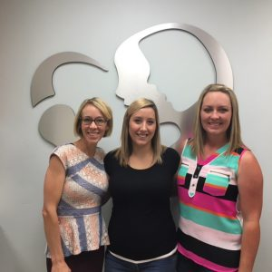 three women smiling in front of the Idaho Fertility Center logo