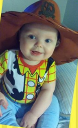baby wearing a Toy Story Woody costume, smiling
